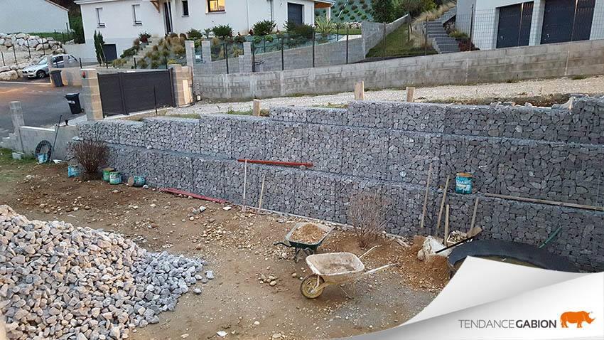 Tendance Gabion, création d'un mur de soutènement à hauteurs variables, de 1,5m à 2,5m, avec décalage de chaque rang pour une meilleure résistance aux poussée.